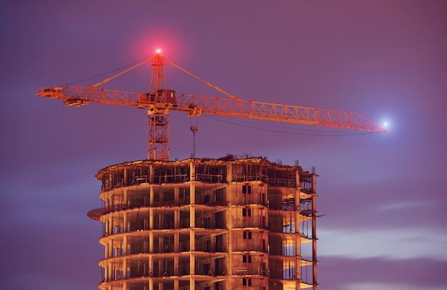Budowa budynku za pomocą dźwigów w nocy