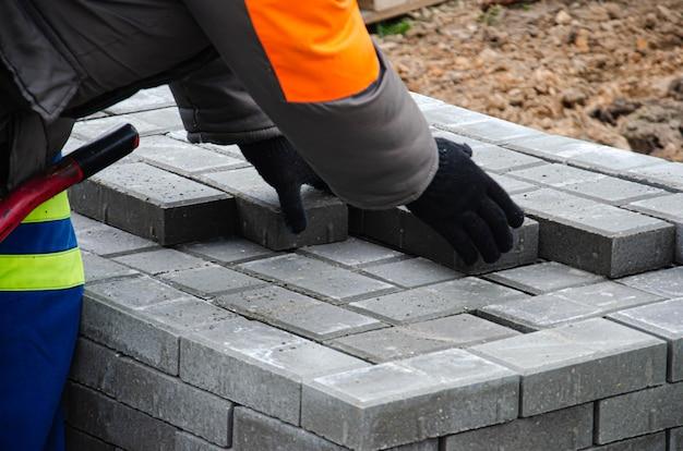 Budowa chodnika przy domu. murarz układa betonową kostkę brukową do budowy chodnika