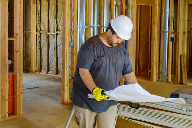 Budowa domu inżynier budowlany sprawdza plan pracy projektu budowlanego.