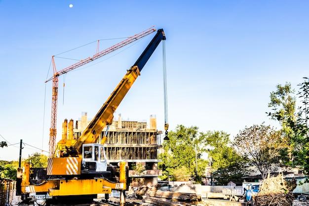 Budowa nowego budynku, dźwigu i podnośnika zamarznięte na tle błękitnego nieba z księżycem