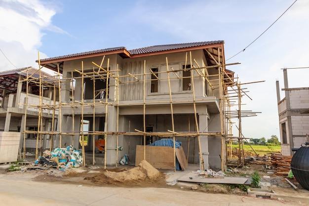 Budowa nowego domu mieszkalnego w toku na budowie z chmurami i błękitne niebo