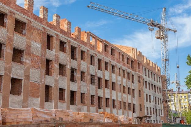 Budowa nowego mieszkania wysoki budynek z żurawiami wieżowymi przeciw błękitne niebo. zabudowa mieszkaniowa. koncepcja rozwoju projektu nieruchomości