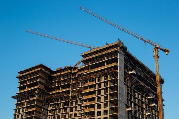 Budowa nowego nowoczesnego wieżowca, kilka dźwigów budowlanych na tle ściany błękitnego nieba