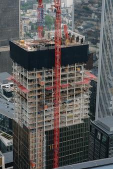 Budowa nowoczesnego wieżowca z dźwigami w centrum metropolii. budowa