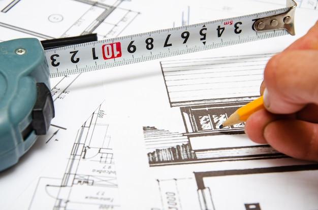 Budowa planu budynku, finansowanie budowy, paczki dolarów, rysunek budynku na papierze, rysunki zwinięte w rulon.