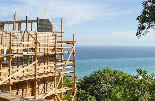 Budowa prywatnego domu lub hotelu na plaży, budowa ścian, rusztowania, słoneczny letni dzień.