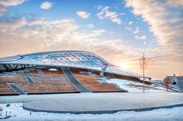 Budowa sali koncertowej w żariadach w moskwie i poranne wiosenne błękitne niebo ze słońcem
