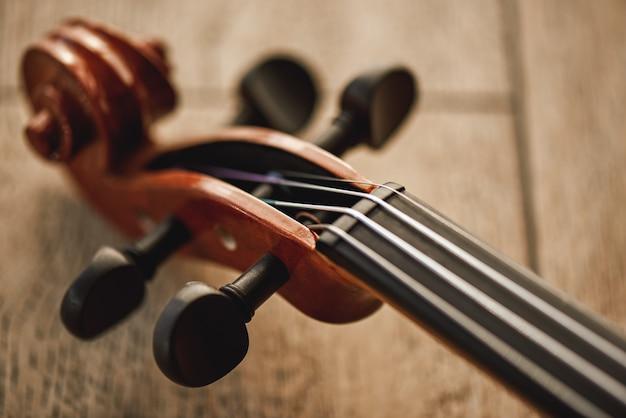 Budowa skrzypiec. widok z góry na szyję skrzypiec leżącego na drewnianym tle. instrumenty muzyczne. sprzęt muzyczny. muzyka w tle