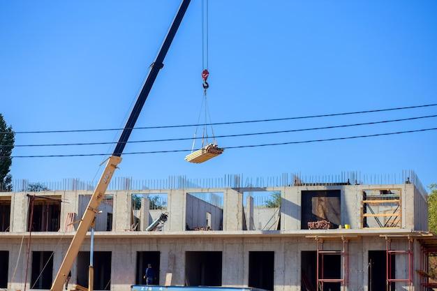 Budowa wielokondygnacyjnego budynku w mieście. żuraw podnosi ładunek na placu budowy budynku