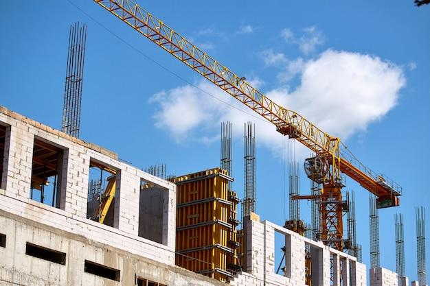 Budowa wieżowca, formowanie podparć cementowych i działanie żurawia na tle błękitnego nieba, selektywne ustawianie ostrości