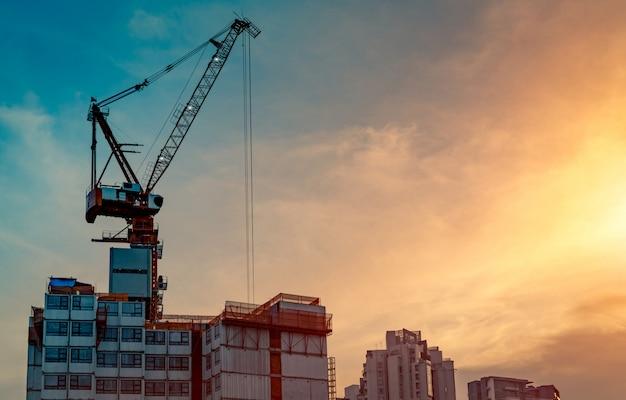 Budowa z żurawiem i budynkiem. przemysł nieruchomościowy. żuraw używa sprzętu do podnoszenia szpul na placu budowy. roboty budowlane w zakresie dźwigów.