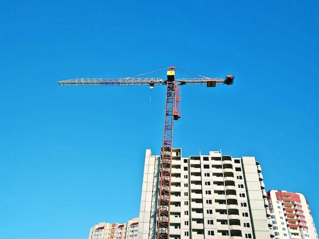 Budowa żuraw przy niebieskim niebem i niedokończonym budynku domem