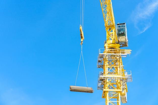Budowa żurawie i wieżowiec w budowie przeciw niebieskiemu niebu.