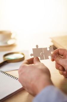 Budowanie sukcesu w biznesie. ręce z łamigłówkami