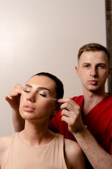 Budowanie twarzy. lekarz z atrakcyjną modelką. operacja blepharoplastyki.