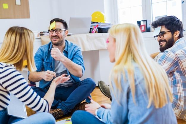 Budowanie zespołu. grupa kolegów siedzi w kręgu i grając w gry i dobrze się bawiąc.