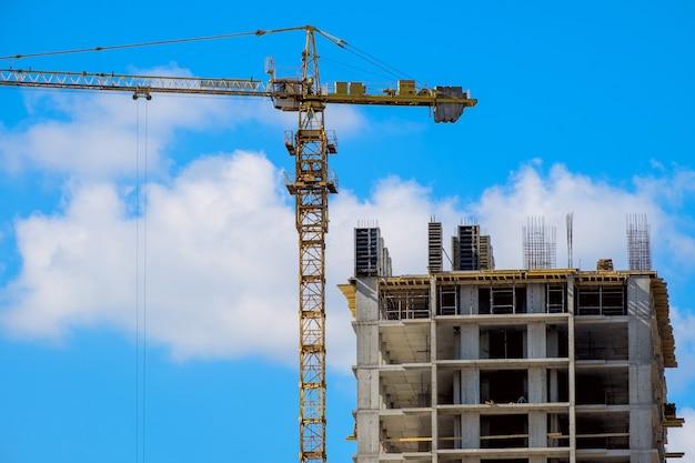 Budowany wieżowiec z żółtym żurawiem budowlanym na tle błękitnego nieba