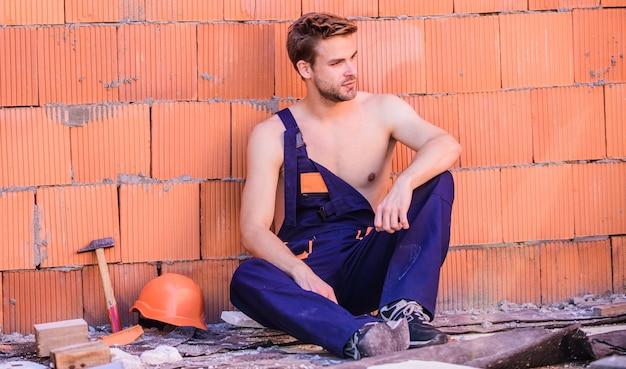 Budownictwo. człowiek zbuduje własny dom. atrakcyjny pracownik. przystojny seksowny robotnik. inspekcja budynku. ogólna konserwacja naprawa pracownik naprawa konserwacja budynku. tło ściany cegła pracownika.