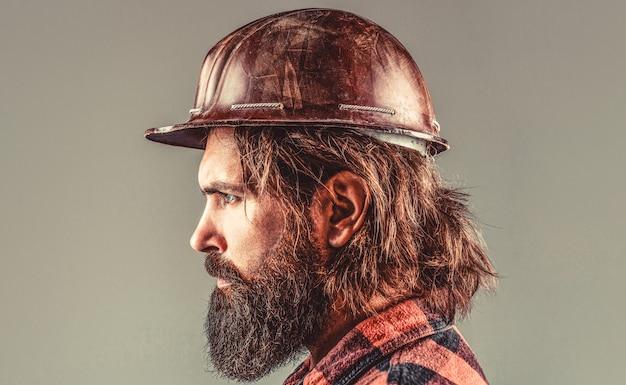 Budownictwo, przemysł, technologia - koncepcja budowniczego. brodaty mężczyzna pracownik z brodą w budynku kasku lub kasku. budowniczowie, przemysł. konstruktor w kasku, brygadzista lub mechanik w kasku