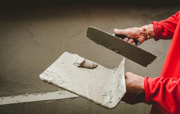 Budowniczowie gipsują ściany domu czystością.