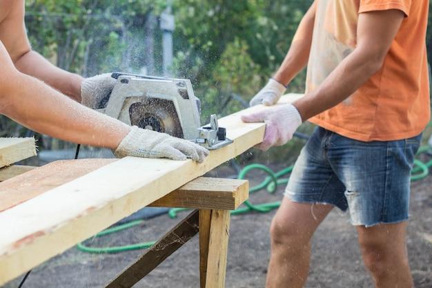 Budowniczowie przecinają deskę piłą tarczową