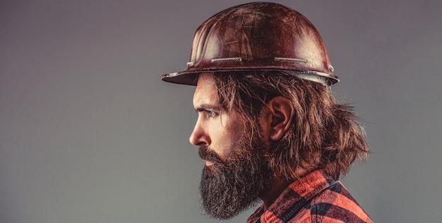 Budowniczowie, przemysł. konstruktor w kasku, brygadzista lub mechanik w kasku. budownictwo, przemysł, technologia - koncepcja budowniczego. brodaty mężczyzna pracownik z brodą w kasku budowlanym lub kasku