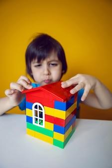 Budowniczy chłopiec dziecko w niebieskiej koszulce na żółtej ścianie buduje naprawę domu z kolorowych plastikowych kostek.