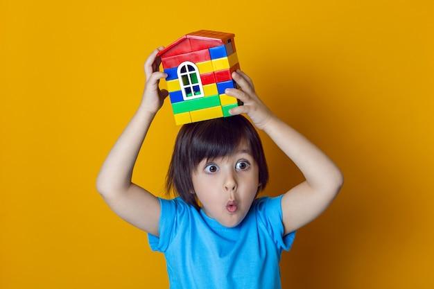 Budowniczy chłopiec dziecko w niebieskiej koszulce na żółtej ścianie trzyma na głowie dom z kolorowych plastikowych kostek