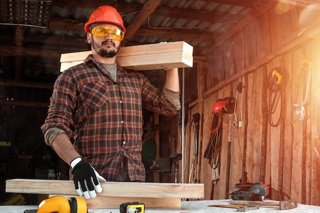 Budowniczy człowiek niesie deski na ramieniu