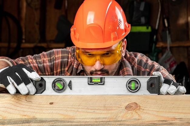 Budowniczy człowiek patrzy na poziom budowy sprawdza poziomą powierzchnię, męskie dłonie z poziomym zbliżeniem.