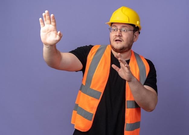 Budowniczy człowiek w kamizelce budowlanej i kasku bezpieczeństwa, patrząc na bok, zmartwiony, trzymając ręce na zewnątrz, stojąc na niebiesko