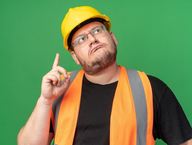Budowniczy człowiek w kamizelce budowlanej i kasku ochronnym patrzący w górę zdziwiony, wskazujący palec wskazujący w górę, stojący nad zielenią