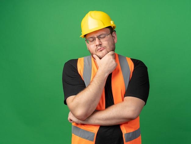 Budowniczy człowiek w kamizelce budowlanej i kasku ochronnym patrzący z zamyślonym wyrazem twarzy z ręką na brodzie, myślący stojąc nad zielenią