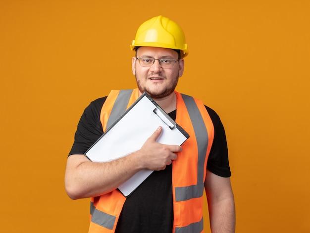 Budowniczy człowiek w kamizelce budowlanej i kasku ochronnym, trzymając schowek, patrząc na kamerę