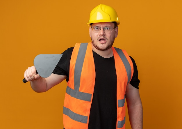 Budowniczy człowiek w kamizelce budowlanej i kasku ochronnym, trzymający szpachlę, patrzący na kamerę, która jest niezadowolona z gniewną twarzą stojącą na pomarańczowym tle