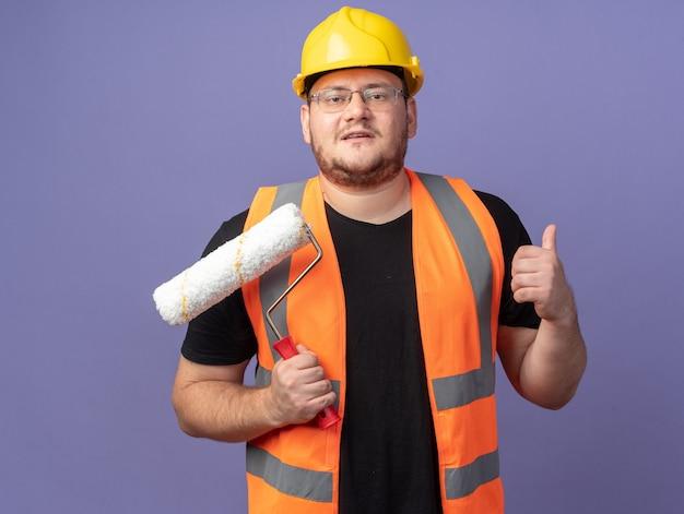 Budowniczy człowiek w kamizelce budowlanej i kasku ochronnym, trzymający wałek do malowania, patrzący na kamerę, uśmiechający się pewnie pokazując kciuk do góry stojący na niebieskim tle