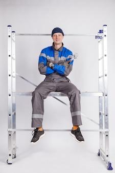 Budowniczy, instalator siedzi na wysokości z narzędziem w ręku