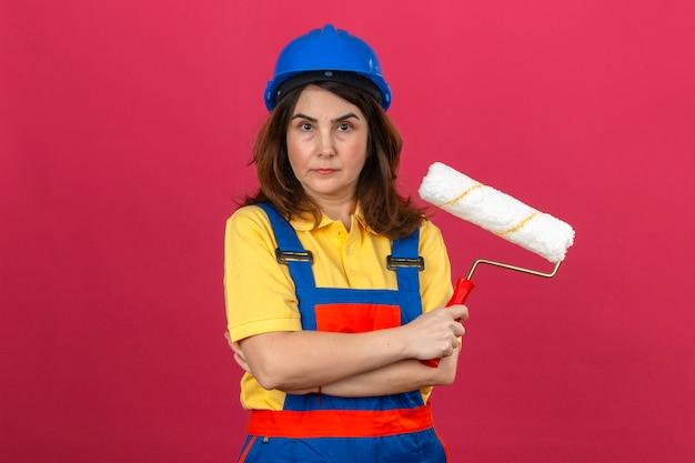 Budowniczy kobieta ubrana w mundur budowlany i kask ochronny, stojąca z rękami skrzyżowanymi z wałkiem do malowania z poważną twarzą na izolowanej różowej ścianie