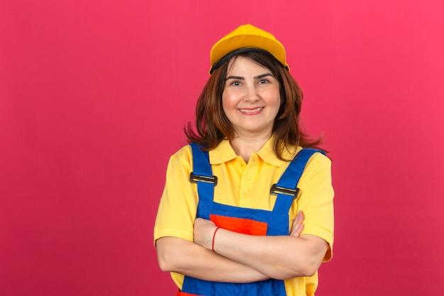 Budowniczy kobieta ubrana w mundur budowlany i żółtą czapkę patrząc pewnie w kamerę, uśmiechając się, stojąc ze skrzyżowanymi rękami, myśląc pozytywnie nad izolowaną różową ścianą