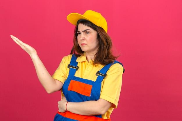 Budowniczy kobieta ubrana w mundur budowlany i żółtą czapkę stojącą z agresywnym wyrazem i ramieniem podniesioną koncepcją frustracji nad izolowaną różową ścianą