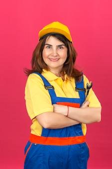 Budowniczy kobieta ubrana w mundur budowlany i żółtą czapkę stojącą z rękami skrzyżowanymi z kluczem uśmiechnięta wesoło na odosobnionej różowej ścianie