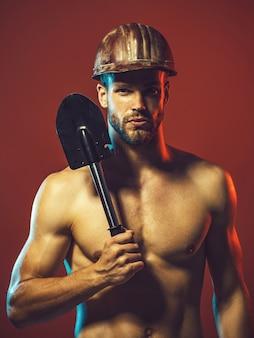 Budowniczy lub górnik nosi kask ochronny z łopatą. robotnik, przemysłowiec, mechanik. budowy mężczyzna portret pracownika posiada łopatę sapera. seksowny budowniczy, inżynier w kasku ochronnym z łopatą.