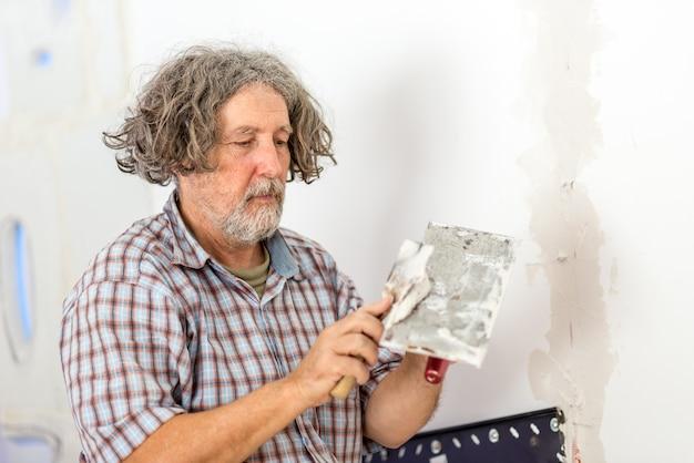 Budowniczy lub właściciel domu w średnim wieku naprawiający ścianę, nakładający szpachlówkę z małej deski za pomocą skrobaka, gdy naprawia pęknięcie lub otwór.