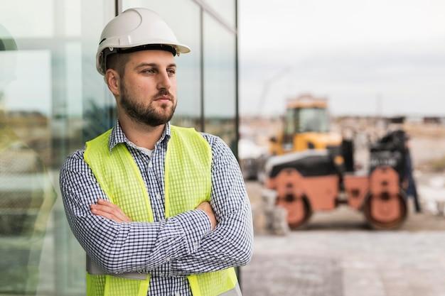 Budowniczy mężczyzna o średnim ujęciu ze skrzyżowanymi rękami