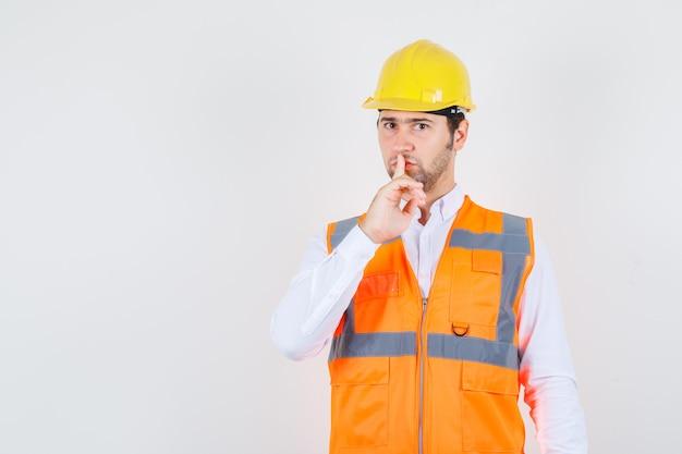 Budowniczy mężczyzna pokazujący gest ciszy w koszuli, mundurze i uważnie wyglądający, widok z przodu.