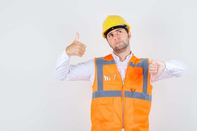 Budowniczy mężczyzna pokazujący kciuki w górę iw dół w koszuli, mundurze i zamyślony, widok z przodu.