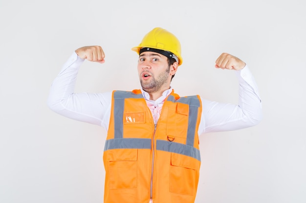 Budowniczy mężczyzna pokazujący mięśnie ramion w koszuli, mundurze i wyglądający silnie, widok z przodu.