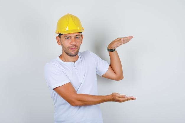 Budowniczy mężczyzna robi duży znak z rękami w białej koszulce, hełm, widok z przodu.