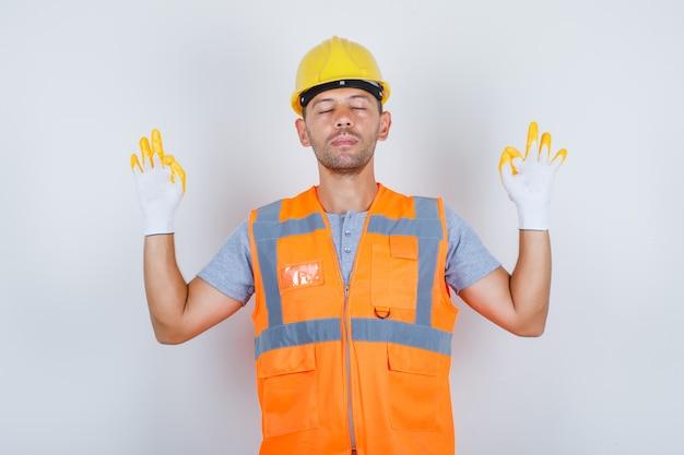 Budowniczy mężczyzna robi medytację z zamkniętymi oczami w mundurze, widok z przodu.