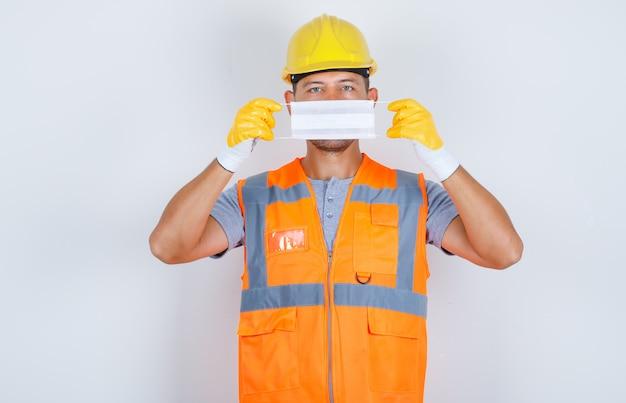 Budowniczy mężczyzna trzyma maskę medyczną na twarzy w mundurze, hełmie, rękawiczkach, widok z przodu.